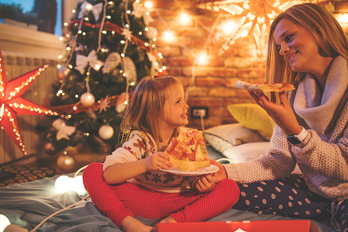Mother and daughter eating pizza in front of Christmas tree