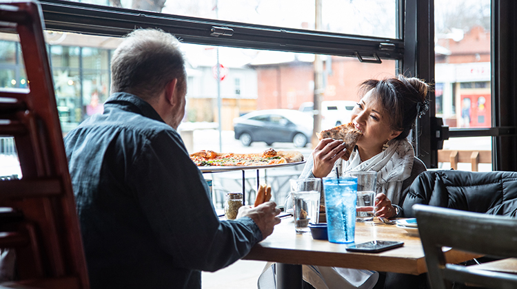 Man and woman eating pizza in pizzeria