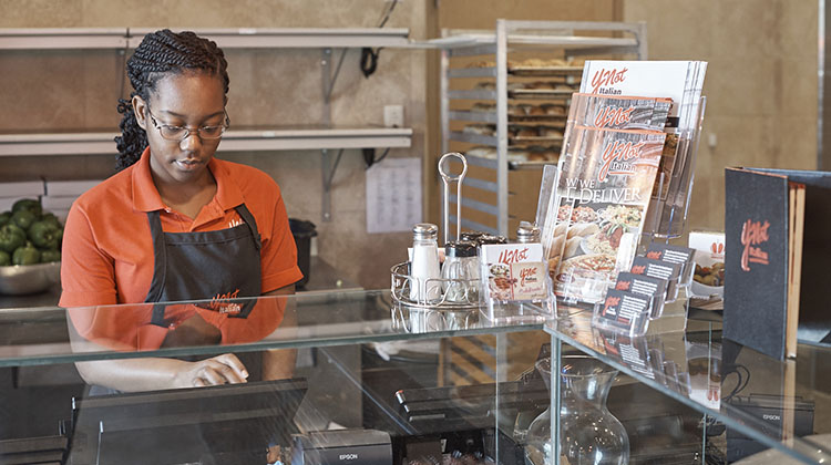 Pizzeria server entering order in POS system